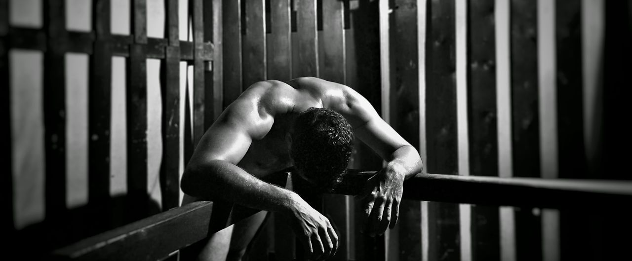 Naked Muscular Man Leaning On Railing By Wooden Wall