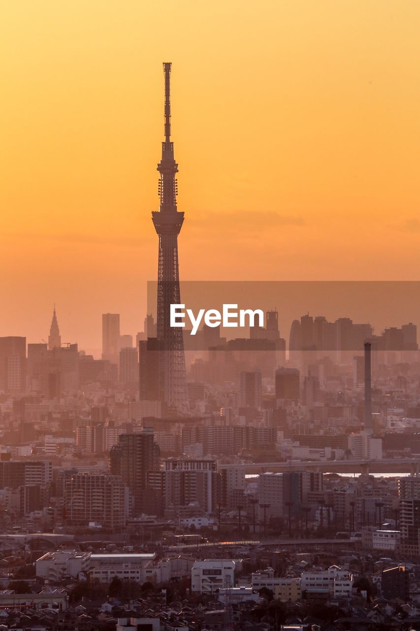 architecture, built structure, building exterior, city, sunset, sky, cityscape, tower, building, orange color, travel destinations, tall - high, no people, nature, office building exterior, skyscraper, sun, outdoors, smog, spire, romantic sky, pollution