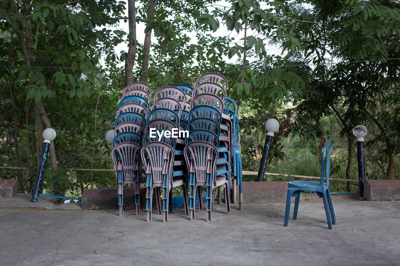 Stack Of Chairs On Footpath Against Trees