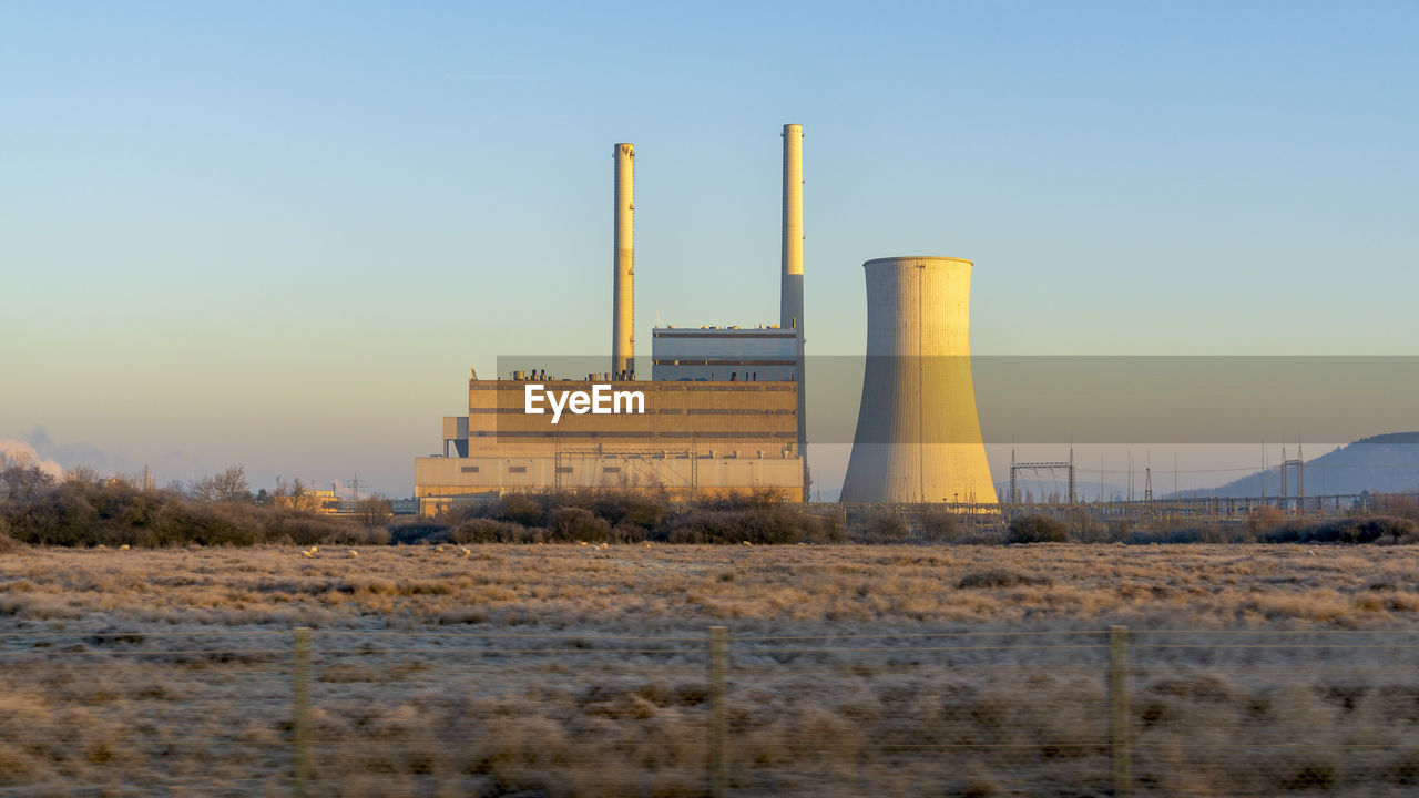 Nuclear reactor at industry against clear blue sky at sunset