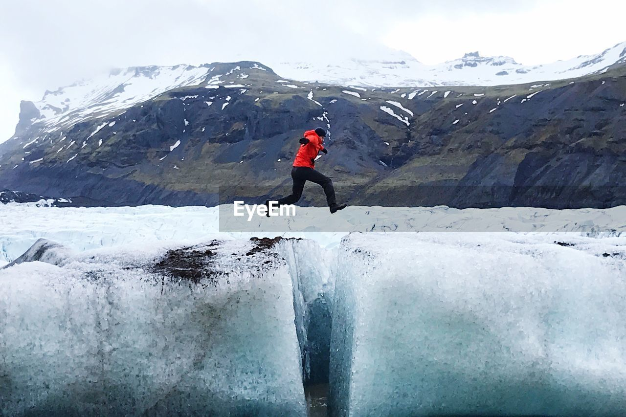 Full Length Of Man Jumping Over Glaciers During Winter
