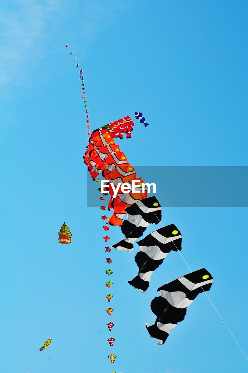 sky, low angle view, blue, multi colored, clear sky, nature, no people, copy space, art and craft, decoration, creativity, day, flying, celebration, outdoors, mid-air, sunlight, kite - toy, craft, design