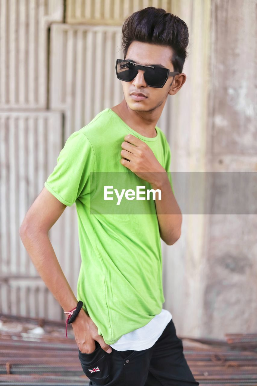 fashion, sunglasses, glasses, one person, real people, standing, three quarter length, casual clothing, young adult, day, focus on foreground, lifestyles, front view, young men, adult, men, green color, clothing, architecture, outdoors