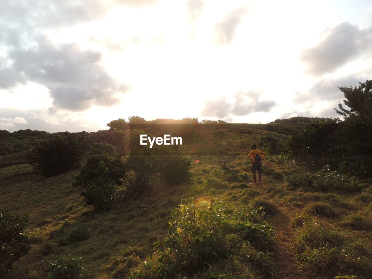Rear view of man hiking on grassy hill against sky