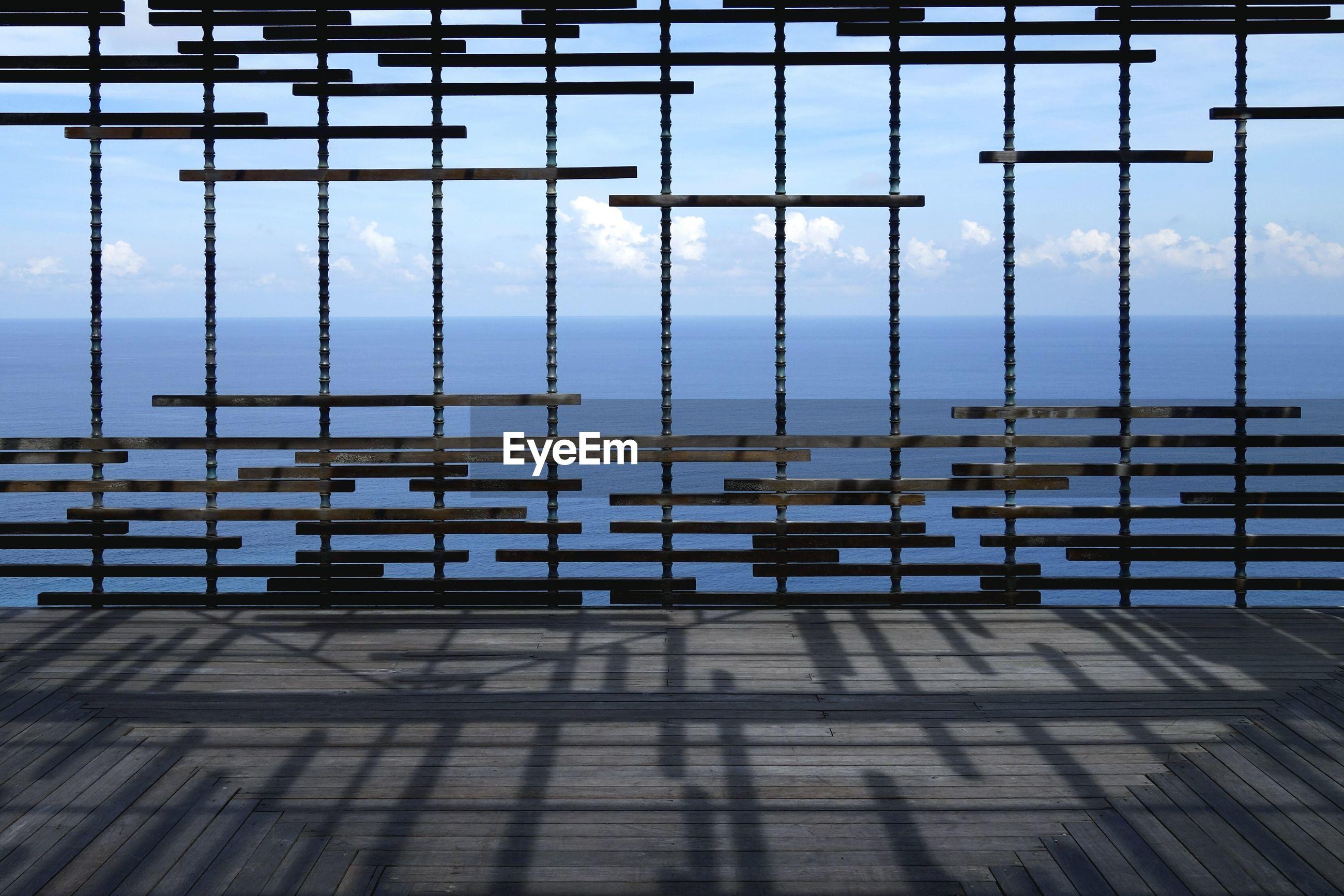 Sea seen through metal grate on pier
