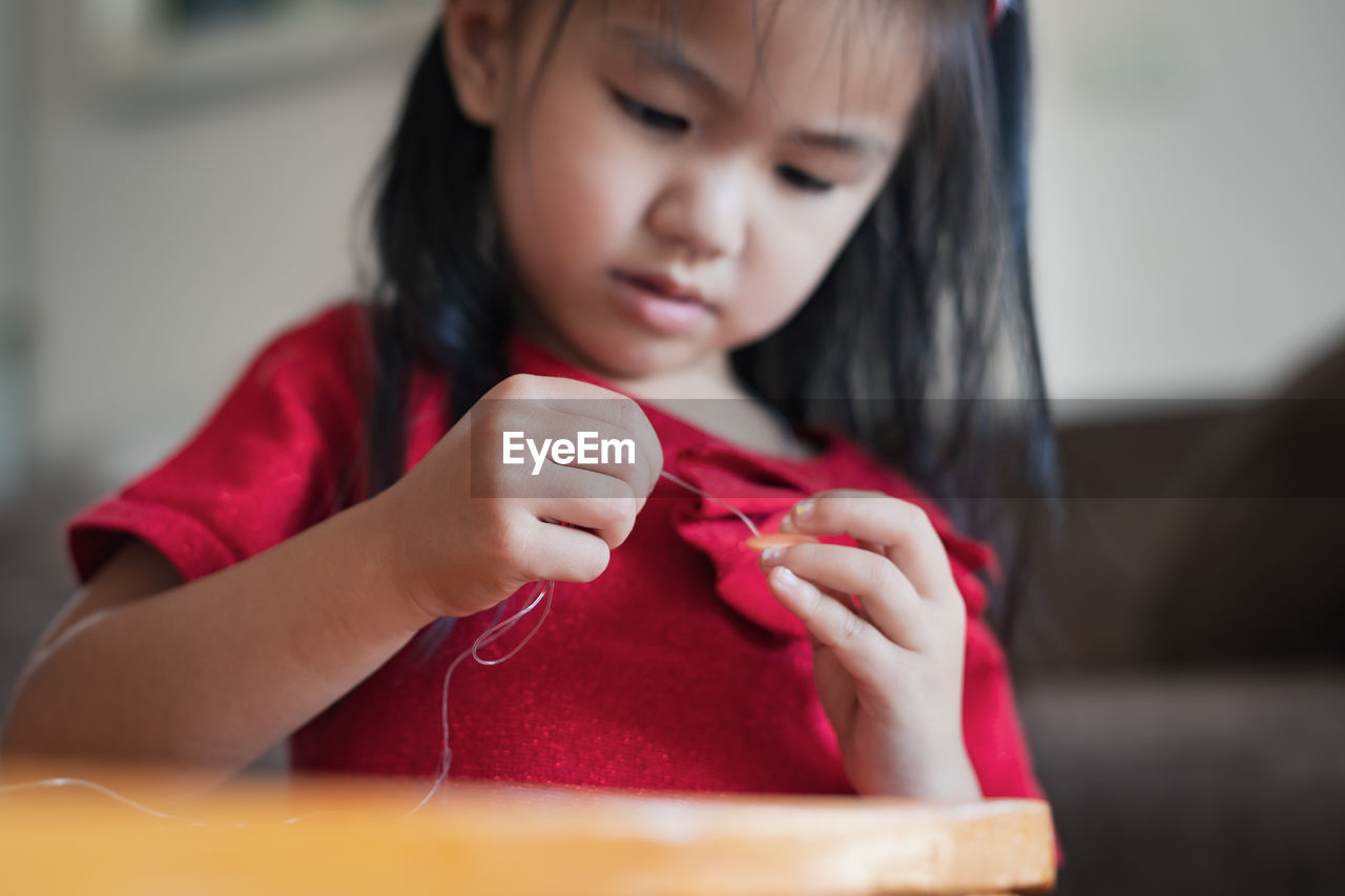 Cute girl doing craft at home