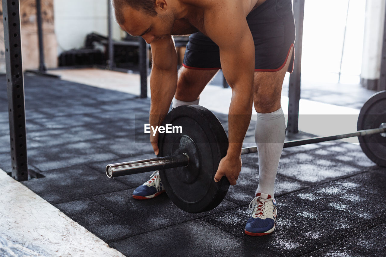 Shirtless Man Holding Barbell At Gym