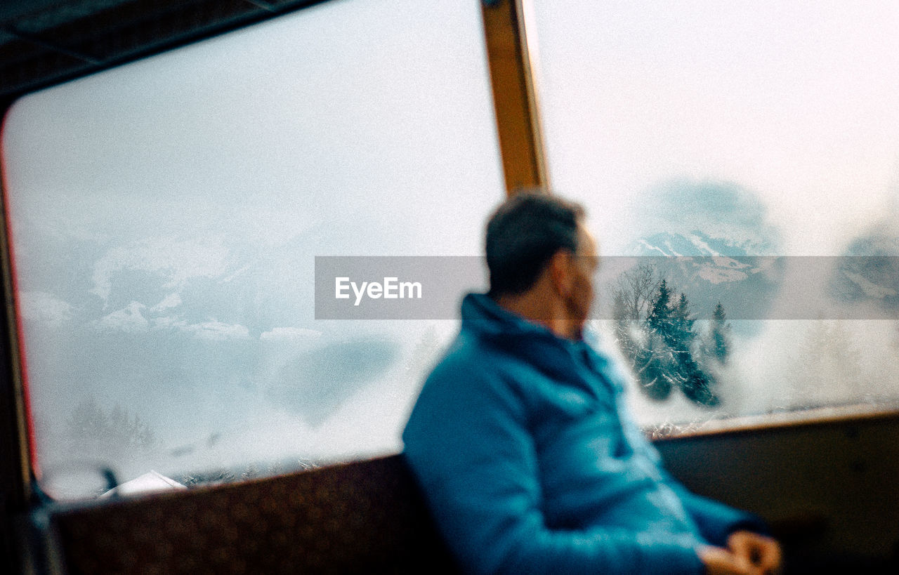 window, winter, real people, one person, transportation, mode of transport, looking through window, sky, cold temperature, day, land vehicle, snow, indoors, women, warm clothing, nature, close-up, people