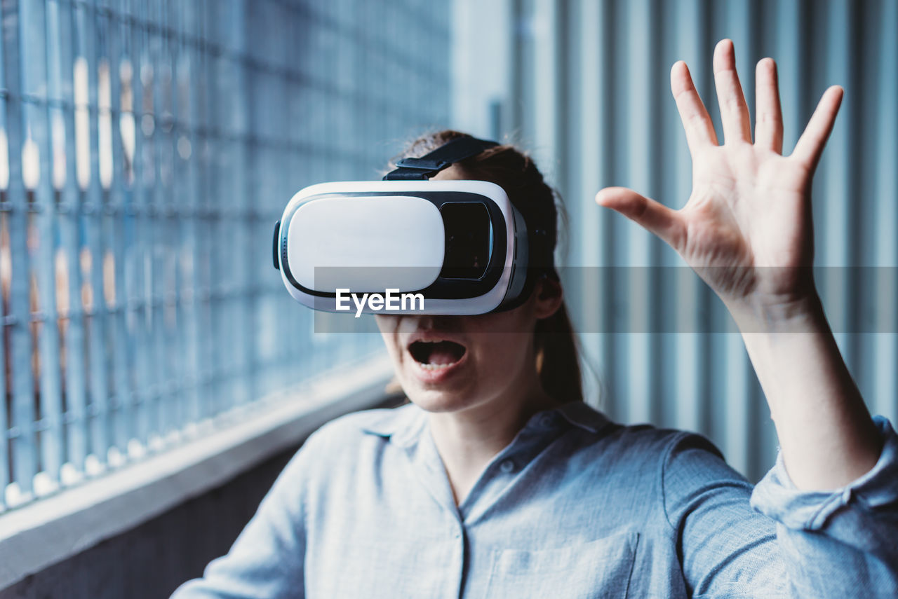 Woman with vr goggles and facial expression enjoying virtual reality experience