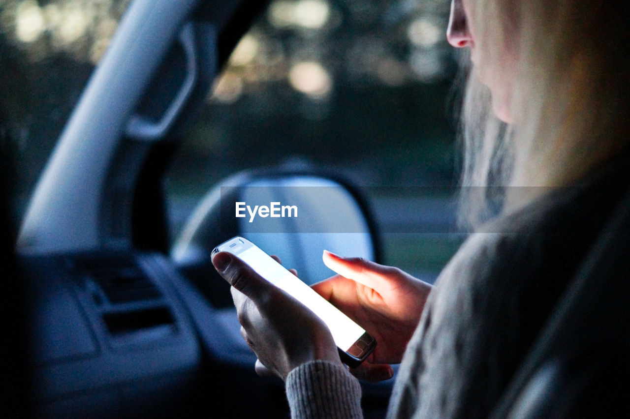 Close-up of woman using mobile phone in car