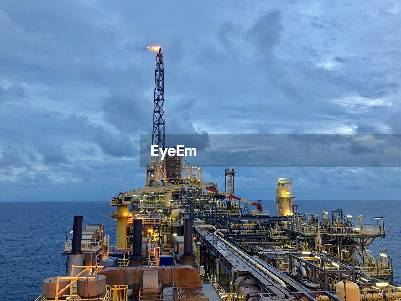 sky, industry, architecture, cloud - sky, oil industry, fuel and power generation, sea, water, built structure, nature, factory, building exterior, offshore platform, no people, business, outdoors, machinery, oil, horizon over water, industrial equipment, pollution