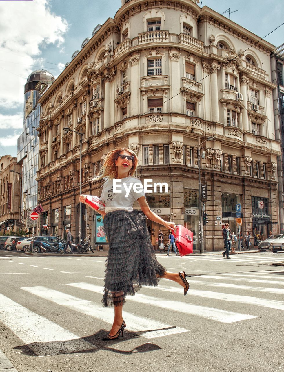 architecture, city, building exterior, street, young adult, built structure, fashion, road, women, full length, one person, young women, looking at camera, beautiful woman, transportation, beauty, adult, lifestyles, real people, city street, hair, hairstyle, outdoors