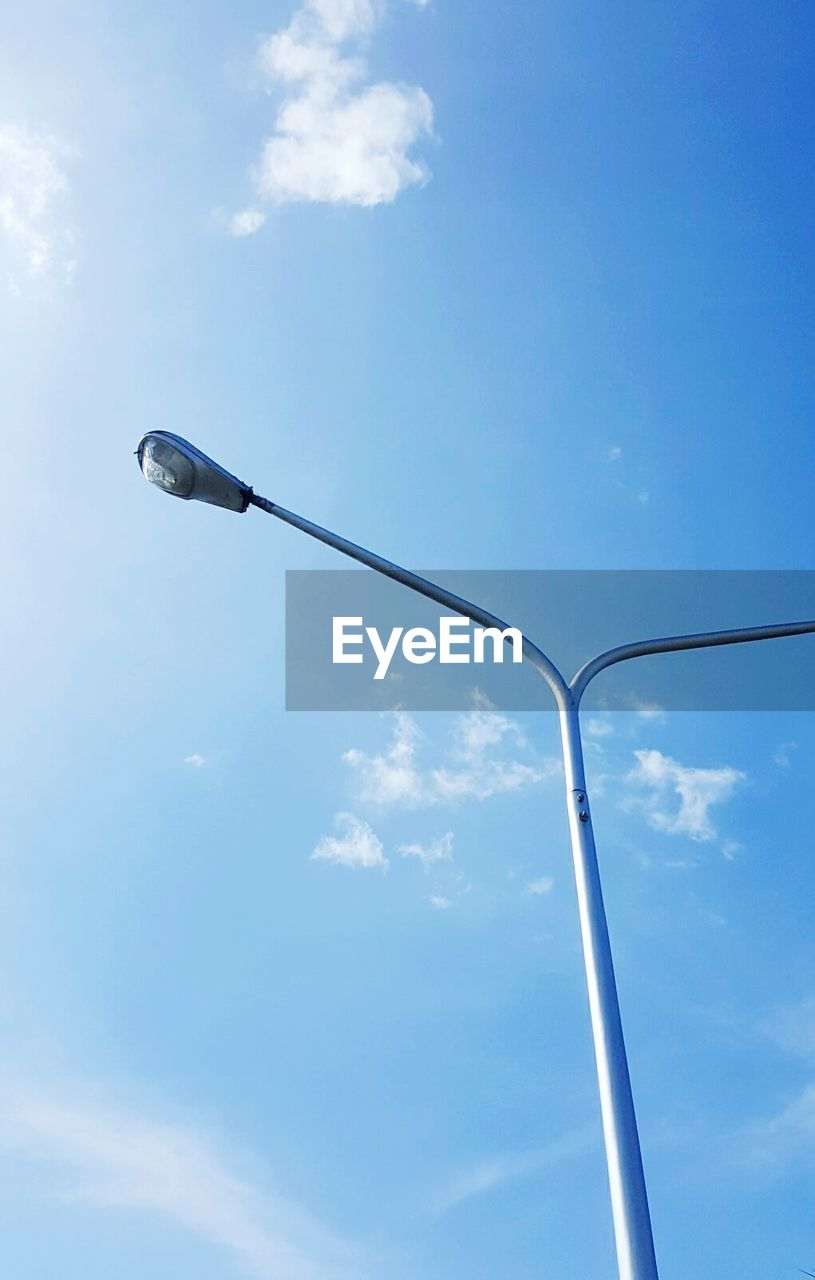 low angle view, sky, cloud - sky, street light, blue, no people, nature, day, lighting equipment, street, pole, outdoors, metal, sunlight, light, technology, copy space, tall - high, full frame, equipment