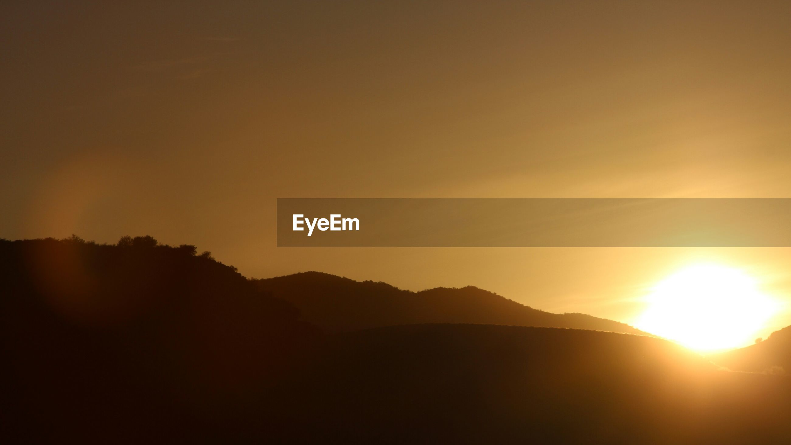 sunset, sun, silhouette, mountain, scenics, tranquil scene, beauty in nature, tranquility, orange color, sunlight, sunbeam, idyllic, nature, mountain range, lens flare, sky, copy space, landscape, clear sky, outdoors