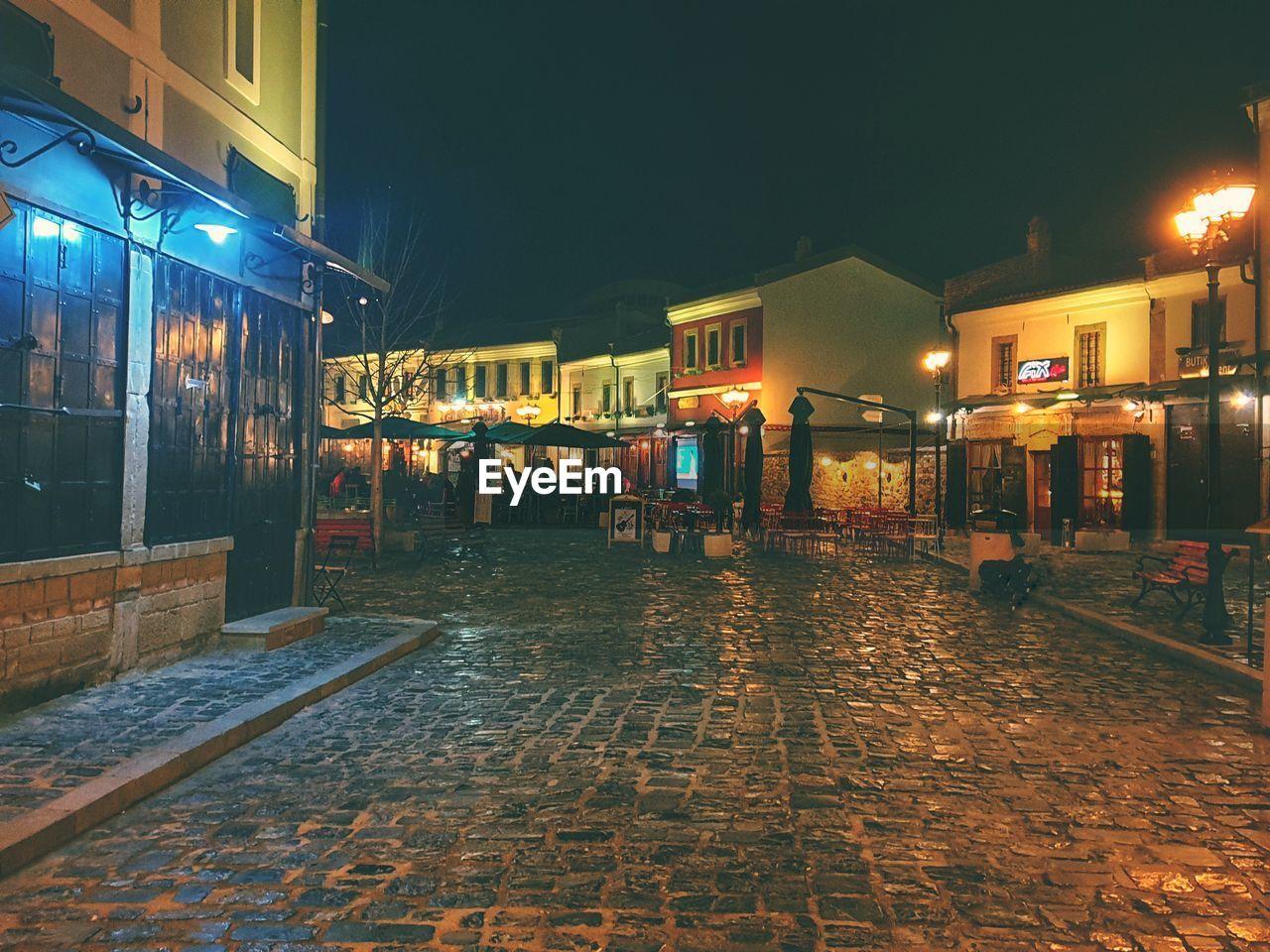 STREET AMIDST ILLUMINATED BUILDINGS AT NIGHT
