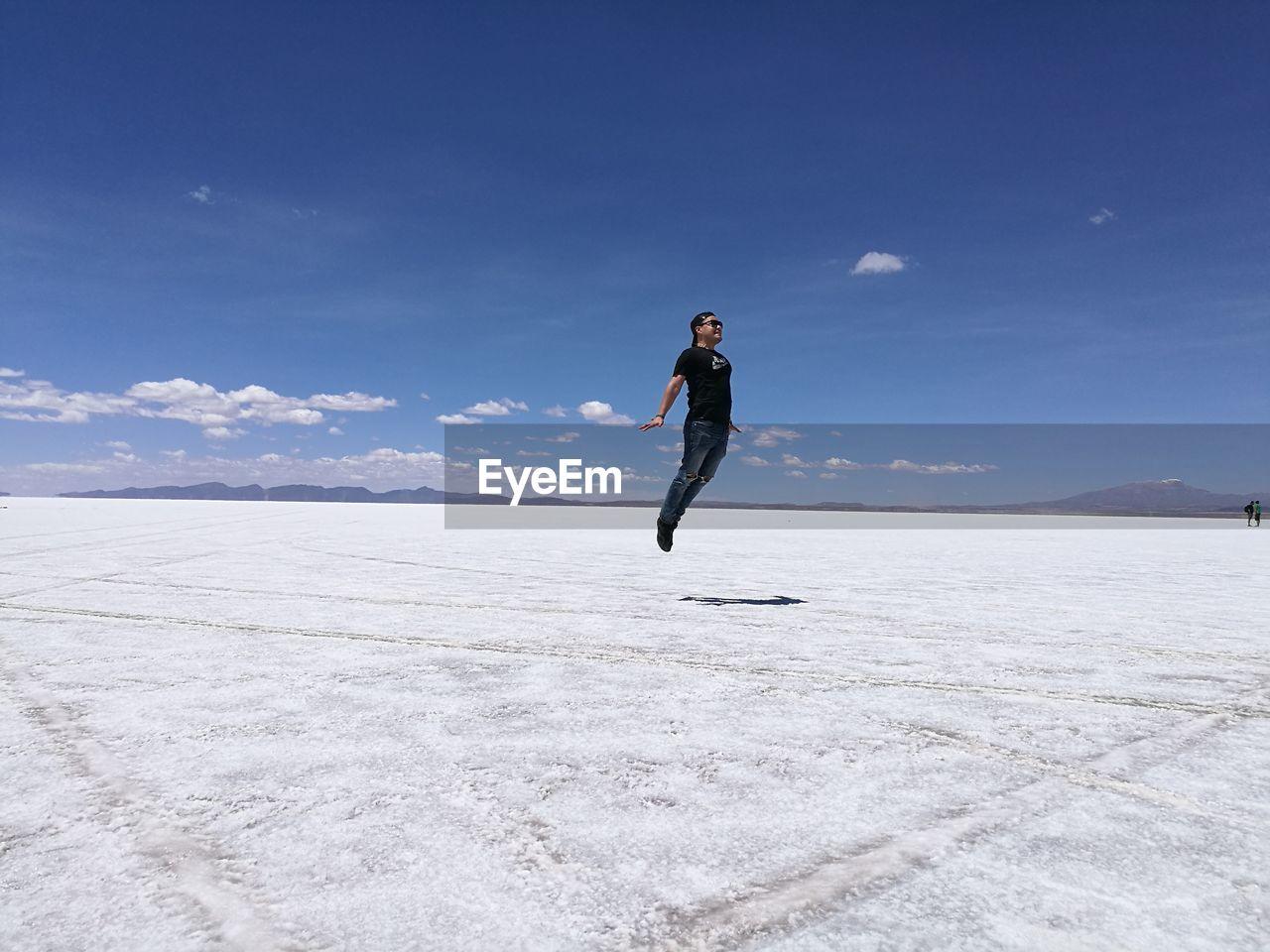 Young Man Levitating On Salt Flat Against Blue Sky At Salar De Uyuni