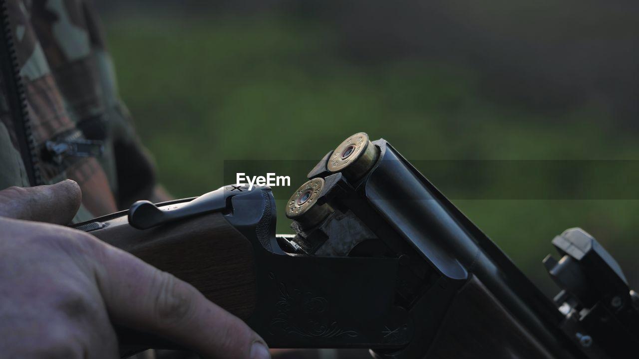 Midsection Of Man Loading Shotgun