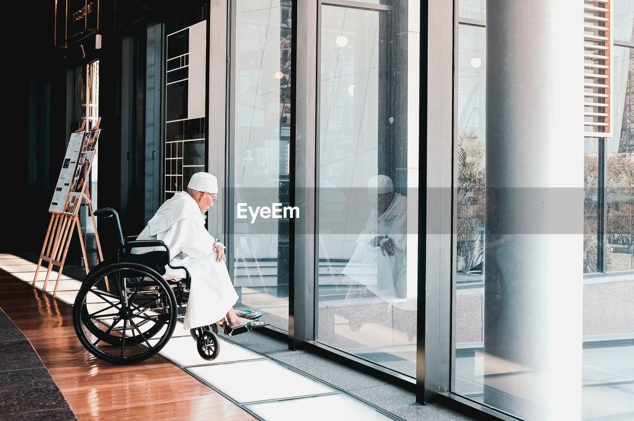 Man Sitting On Wheelchair In Corridor