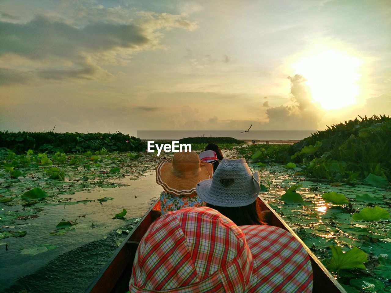 People In Boat On Stream Against Sky During Sunset