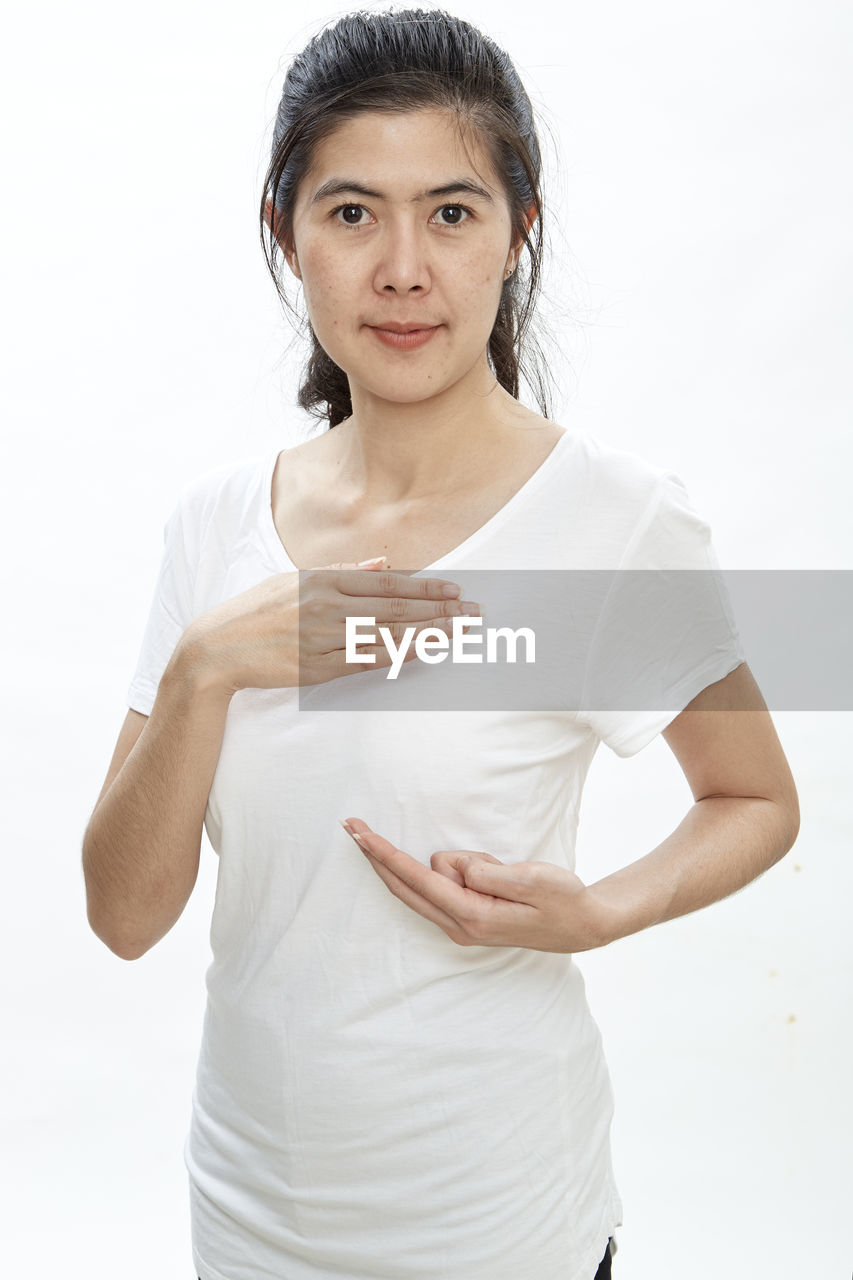 Portrait of woman touching breast against white background