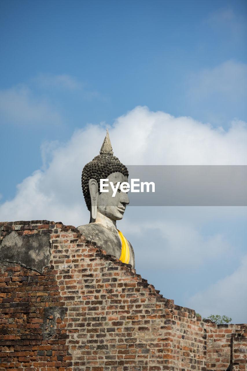 Low Angle View Of Buddha Statue By Old Brick Wall At Wat Yai Chai Mongkhon