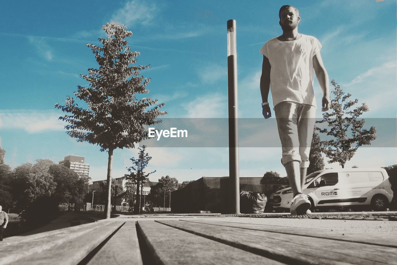 Surface level image of young man walking on street against sky