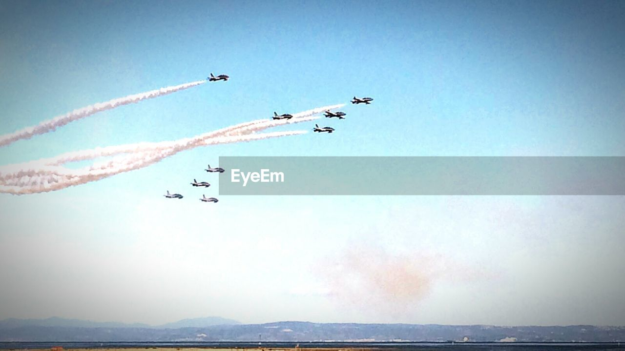 flying, vapor trail, airshow, teamwork, mid-air, smoke - physical structure, speed, airplane, sky, low angle view, air vehicle, transportation, arrangement, togetherness, motion, fighter plane, day, outdoors, cooperation, military airplane, nature, acrobatic activity, blue, performance, no people, coordination, aerobatics