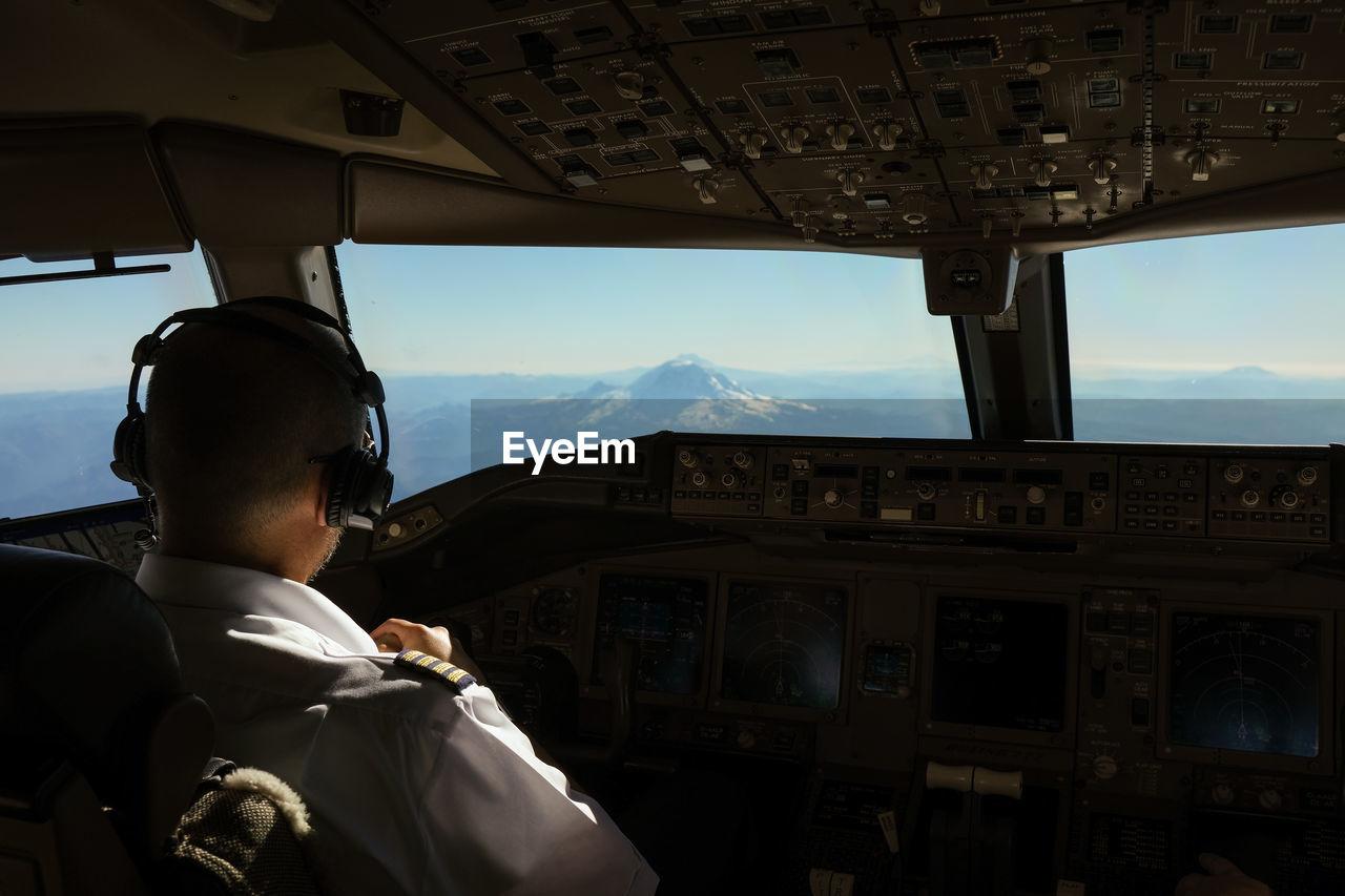Rear view of pilot at aeroplane cockpit