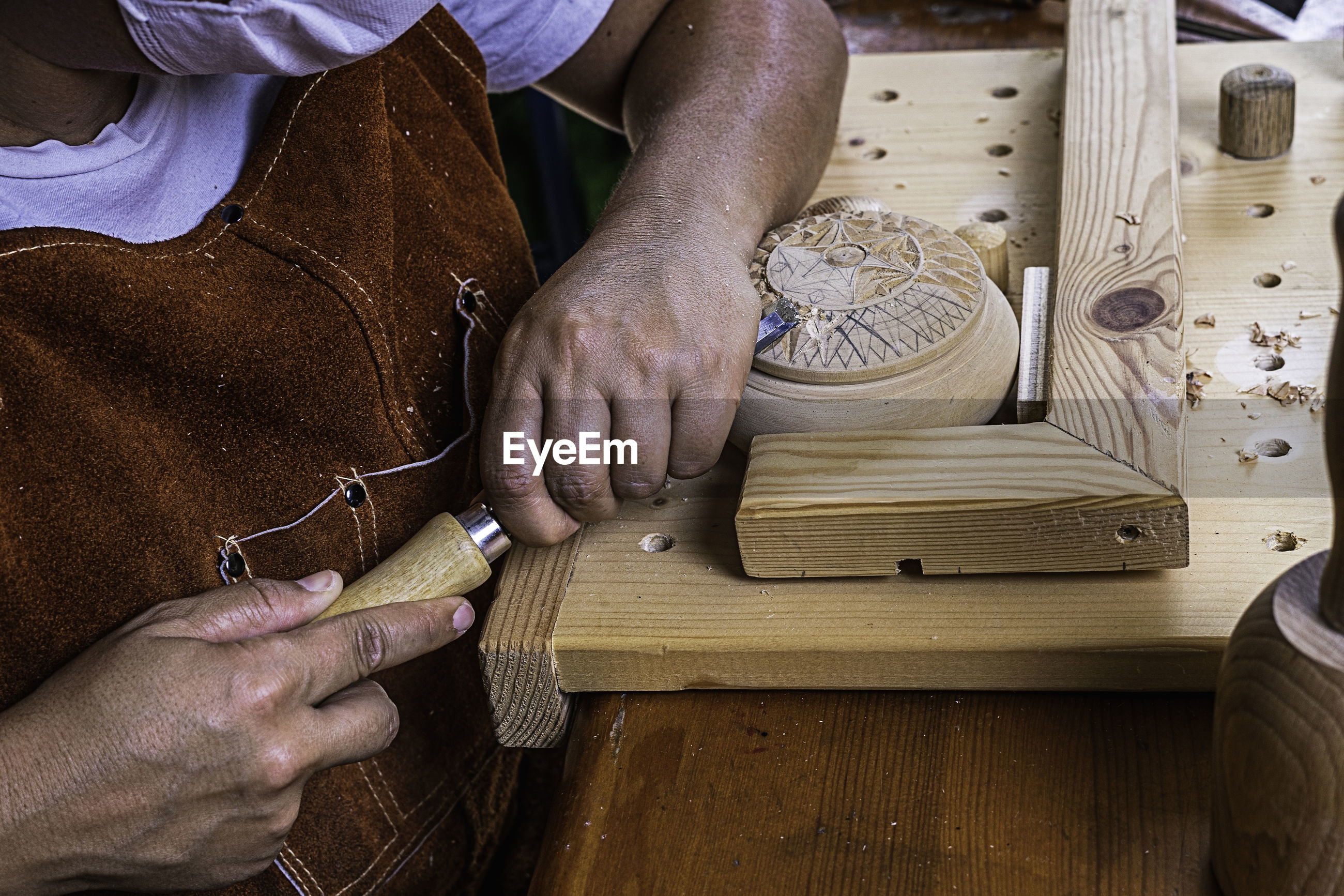 MIDSECTION OF MAN WORKING WITH WOOD