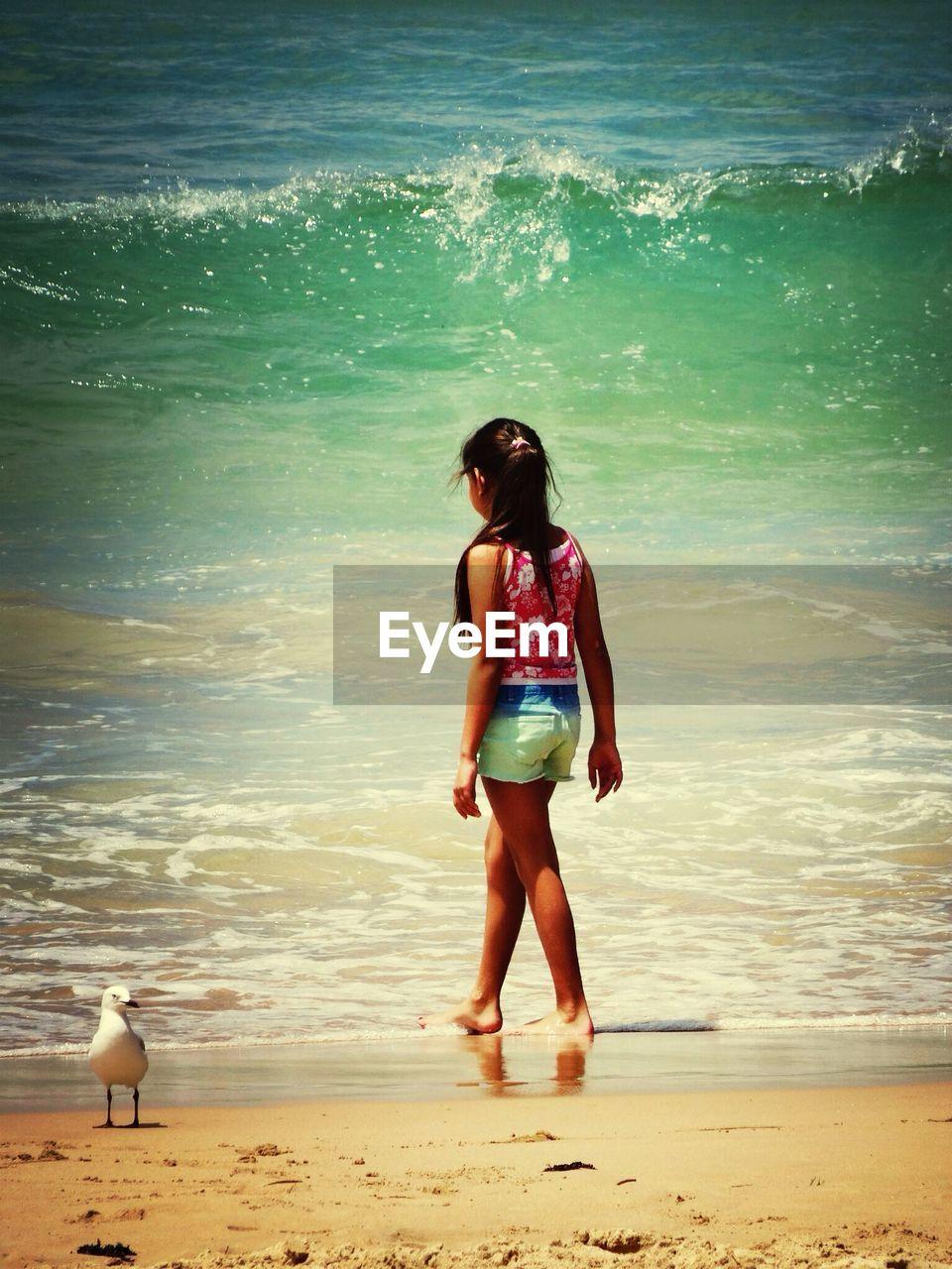 Rear view of girl walking on beach