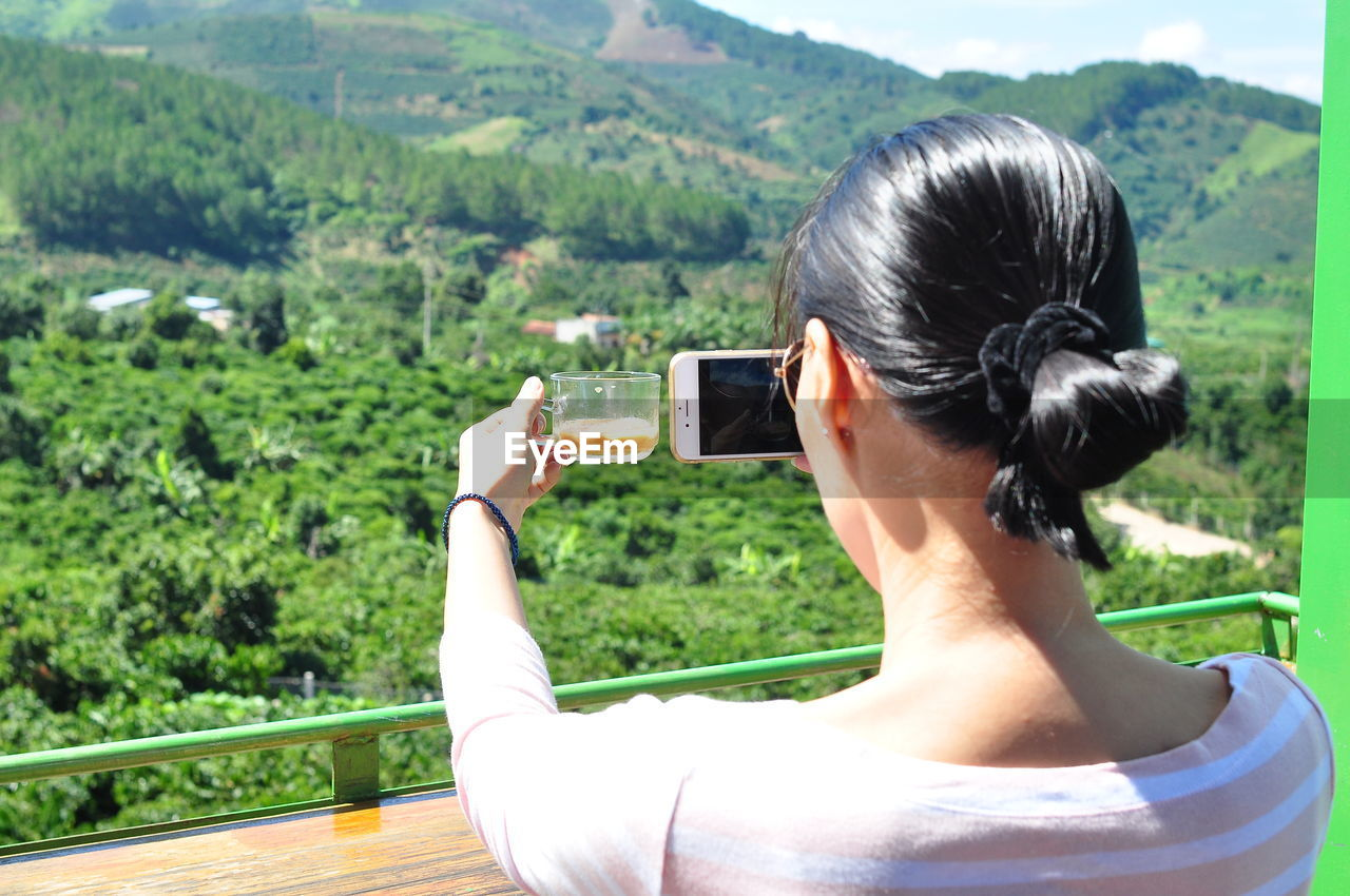 Rear View Of Woman Photographing With Mobile Phone While Holding Coffee Cup