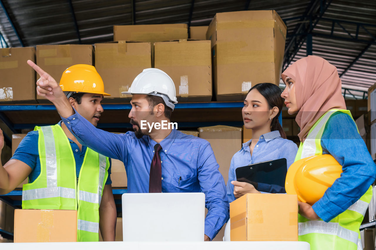 Businessman instructing coworkers in factory