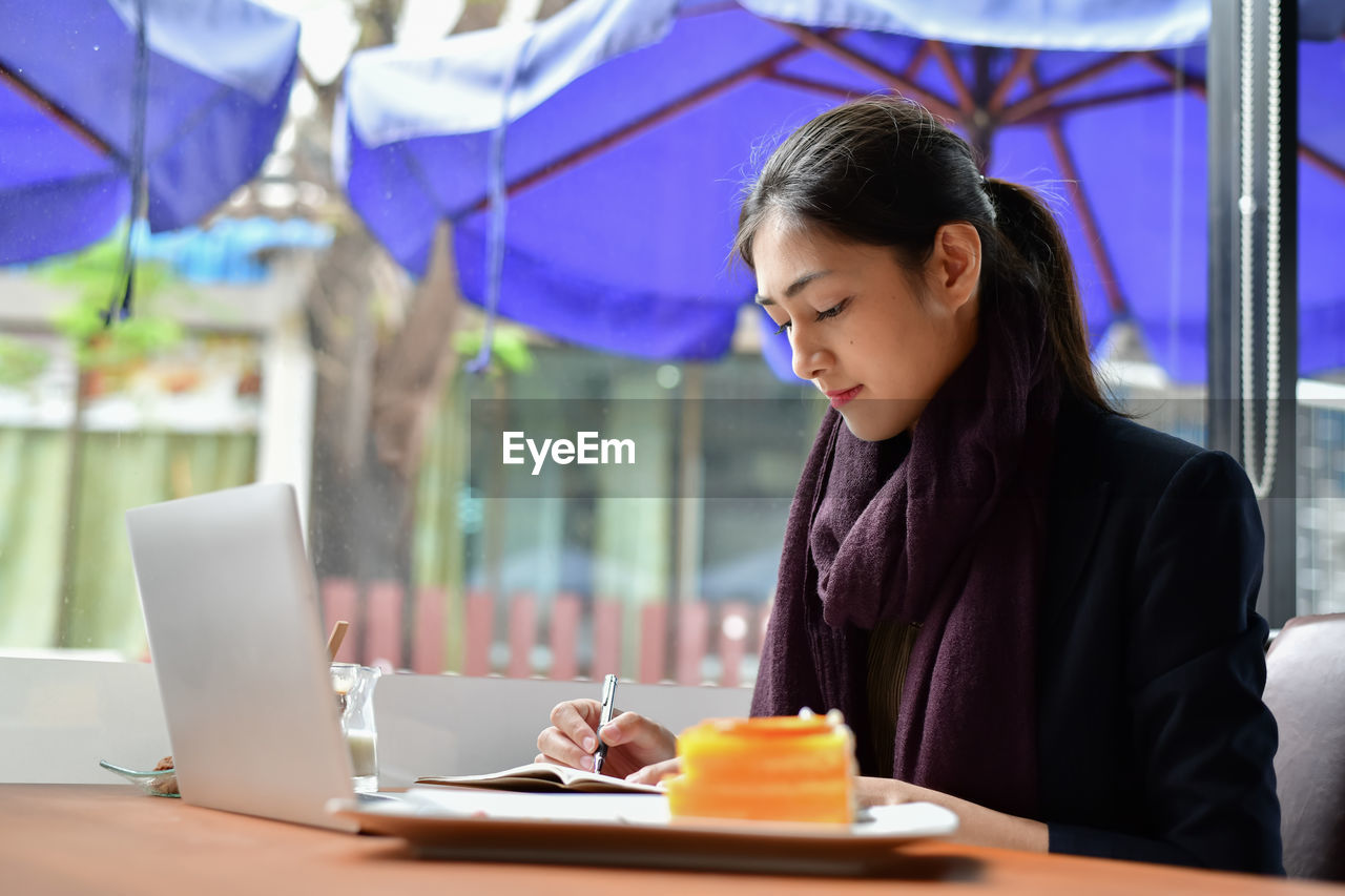 table, business, one person, sitting, real people, food and drink, women, young adult, young women, adult, waist up, connection, restaurant, cafe, communication, business person, laptop, lifestyles, technology, wireless technology, using laptop, hairstyle