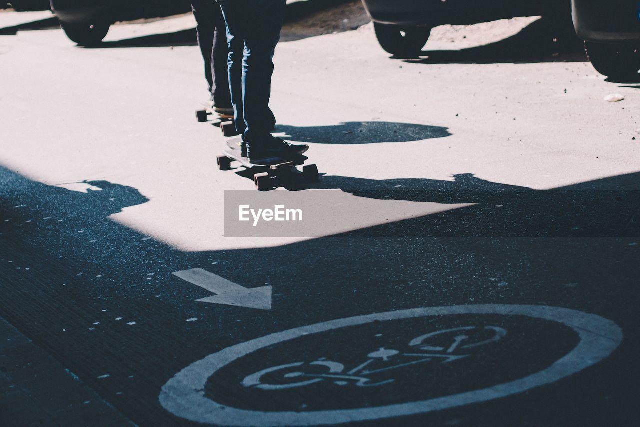 Low Section Of People Skateboarding On Street