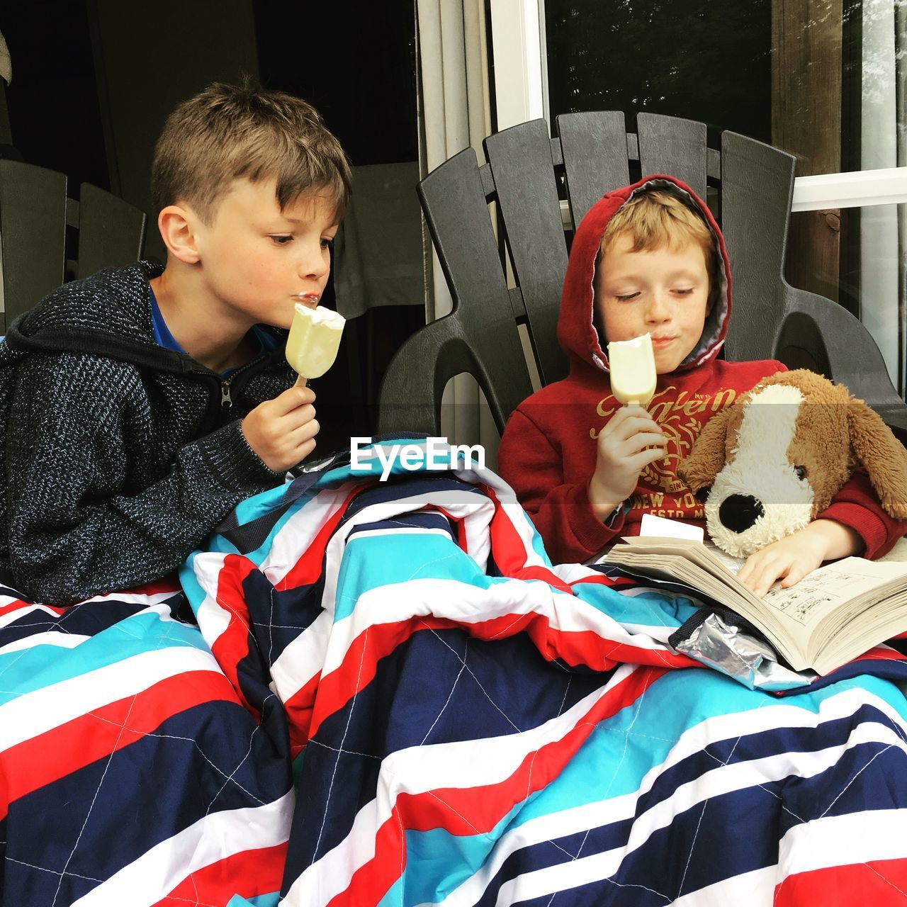 Brothers Reading Book While Eating Ice Cream At Home