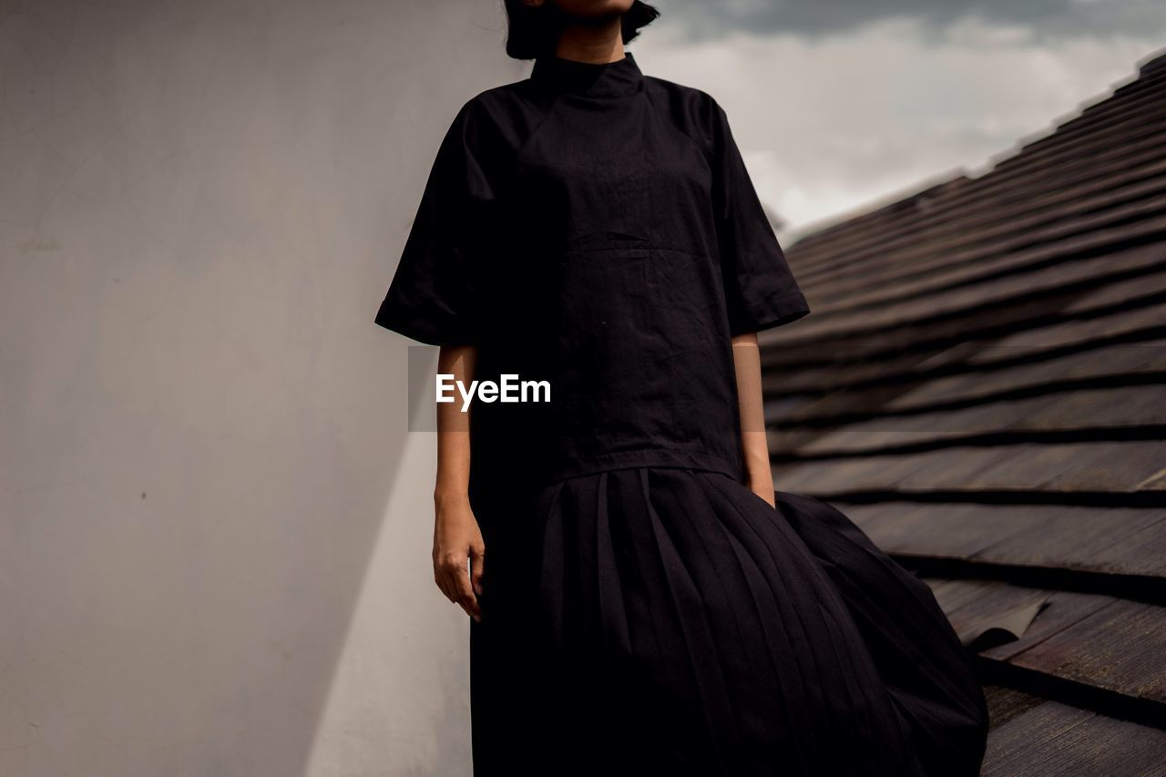 one person, clothing, wall - building feature, dress, real people, fashion, lifestyles, standing, architecture, three quarter length, built structure, black color, adult, casual clothing, leisure activity, men, rear view, women, day
