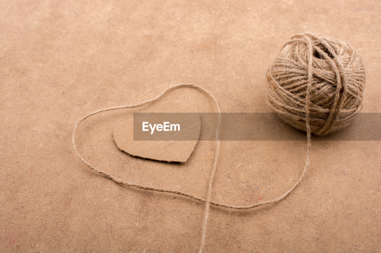 heart shape, love, emotion, positive emotion, no people, string, valentine's day - holiday, studio shot, close-up, simplicity, brown, indoors, shape, high angle view, creativity, still life, rope, directly above, craft