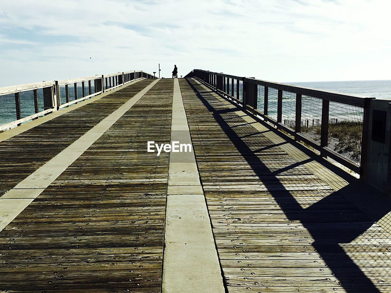 Low angle view of pier on beach and sea against sky