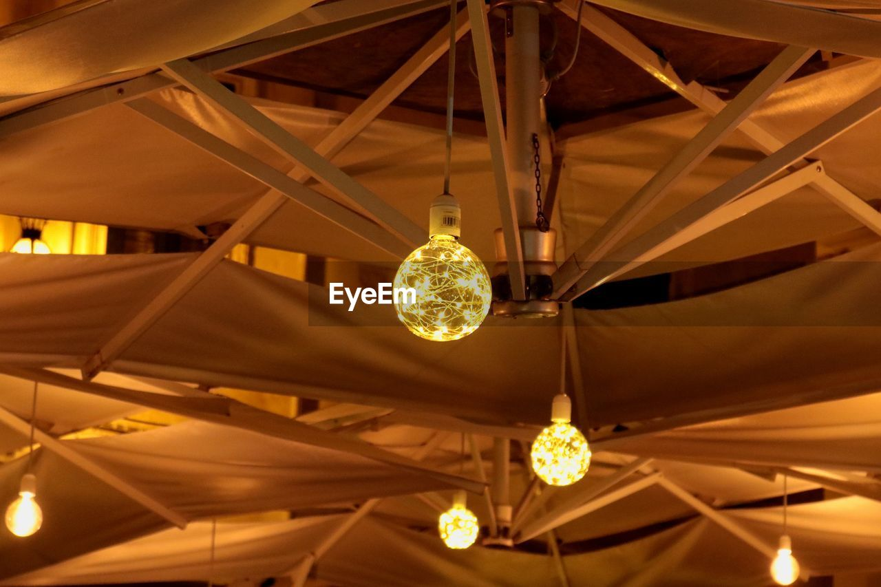 lighting equipment, hanging, illuminated, ceiling, low angle view, indoors, electricity, light, glowing, chandelier, light bulb, no people, electric light, pendant light, decoration, wealth, technology, luxury, focus on foreground, built structure, electric lamp, light fixture, roof beam