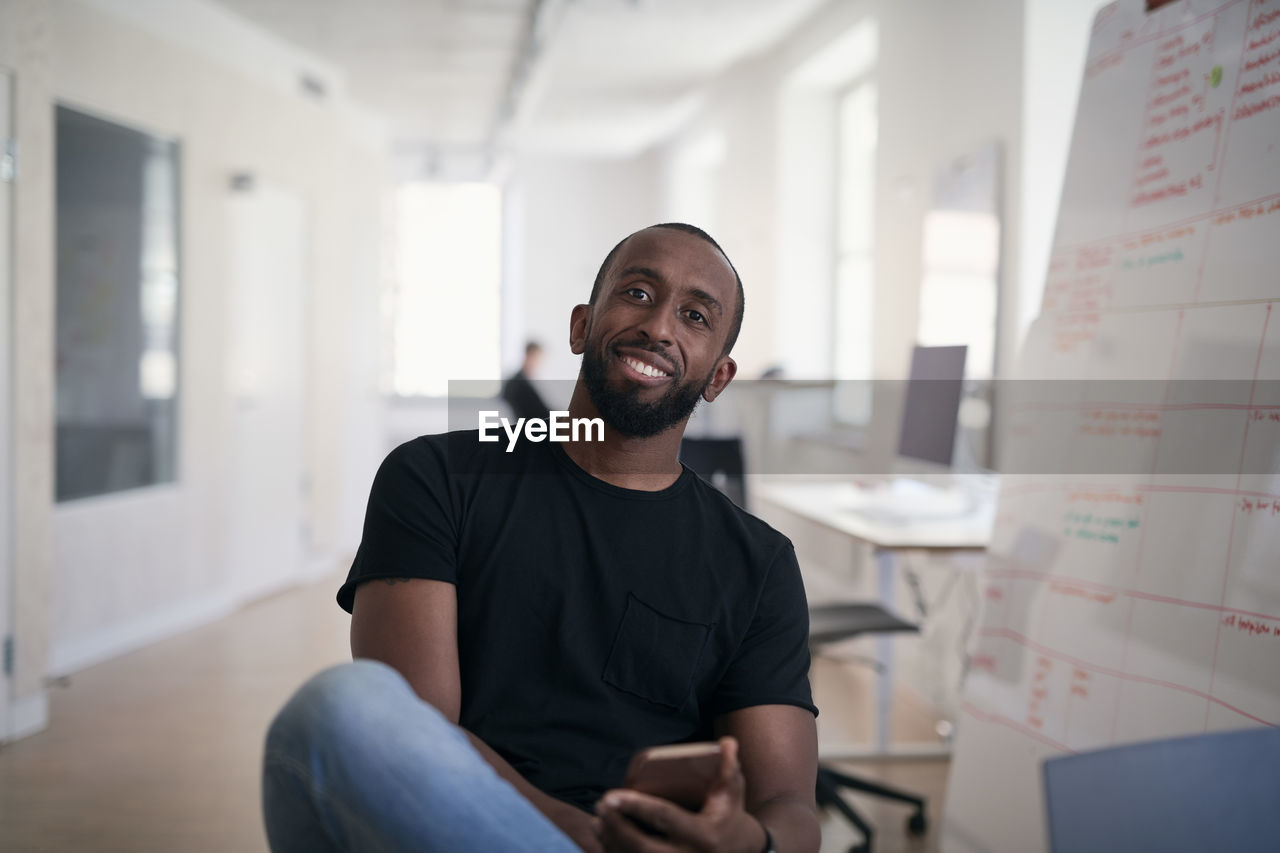 PORTRAIT OF A SMILING YOUNG MAN SITTING IN A ROOM