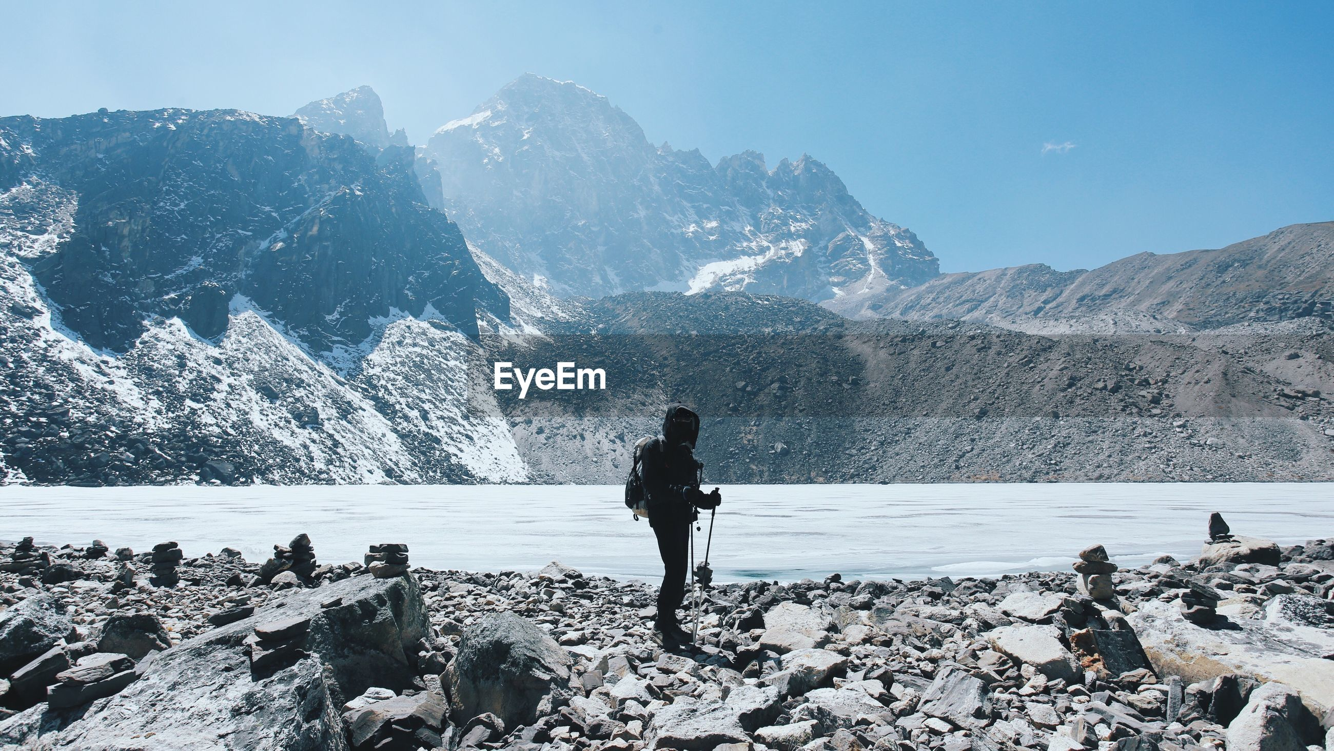 Person standing by gokyo lake against rocky mountains on sunny day