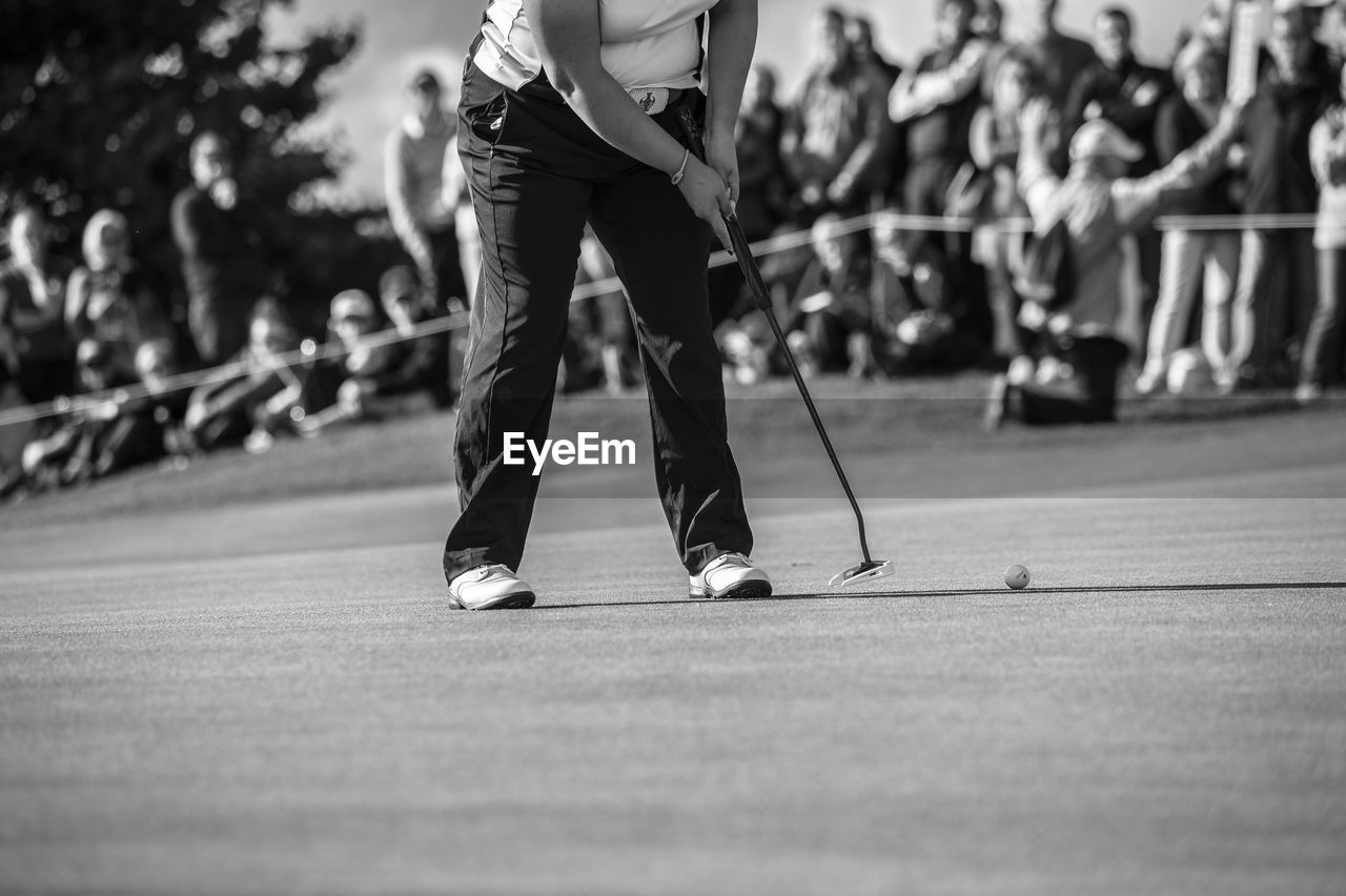 Low Section Of Woman Playing Golf On Field While Audience Enjoying