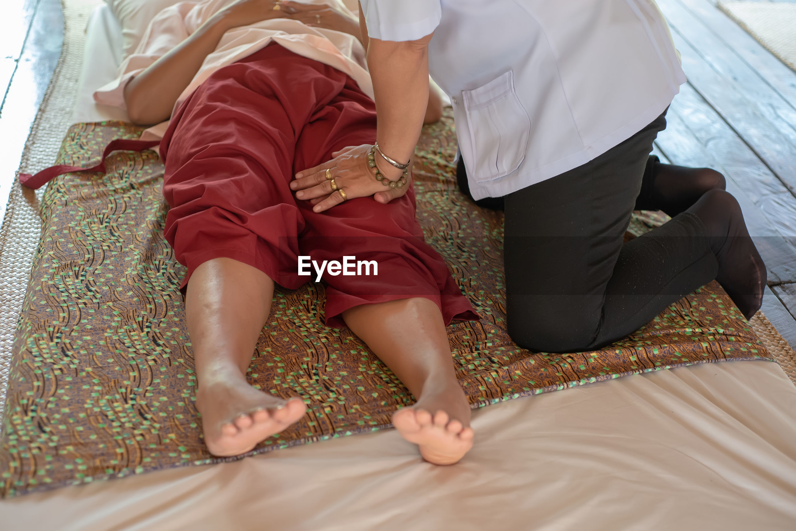 Low section of person giving therapy to woman