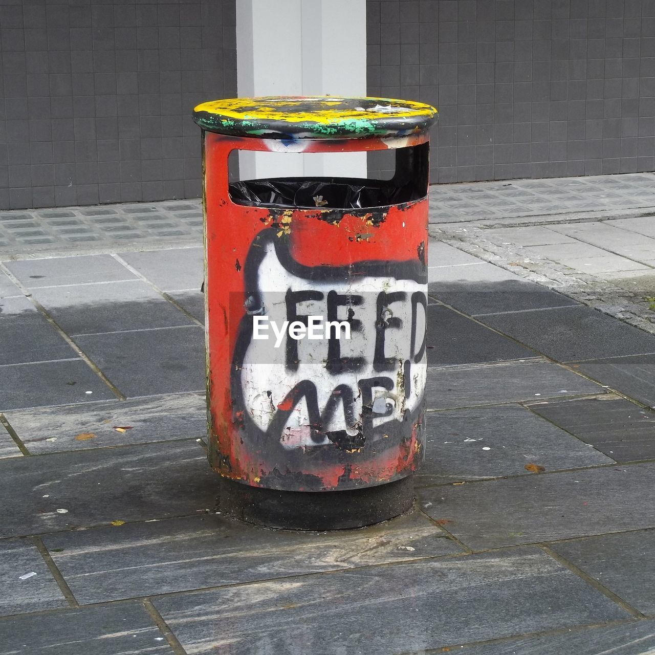 text, day, western script, footpath, no people, street, garbage bin, communication, outdoors, sidewalk, city, garbage can, recycling bin, metal, recycling, road, environmental issues, red, sign, safety