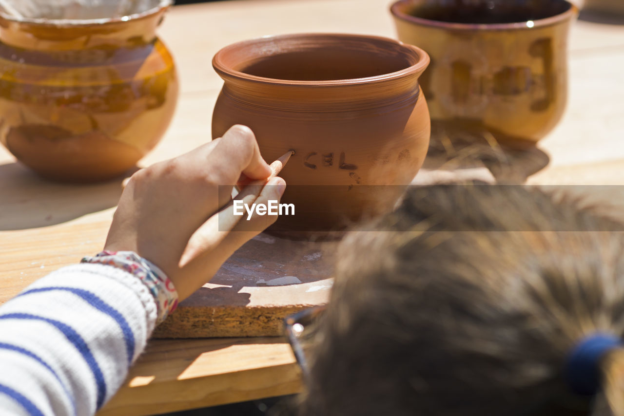 Close-Up Of Girl Writing On Earthen Bowl In Market