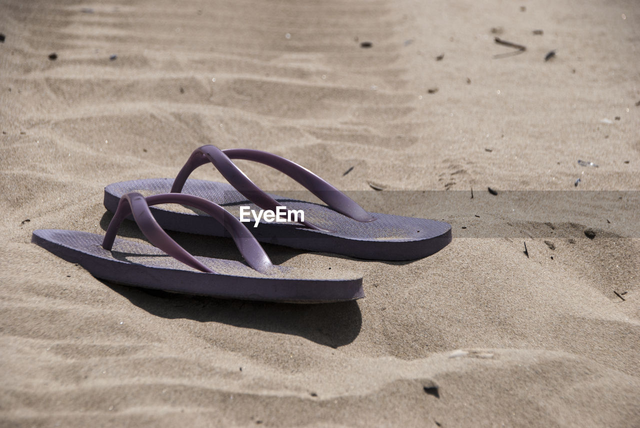 sand, land, beach, shoe, no people, nature, sunlight, pair, absence, sandal, slipper, flip-flop, day, still life, outdoors, close-up, focus on foreground, selective focus, compatibility, personal accessory
