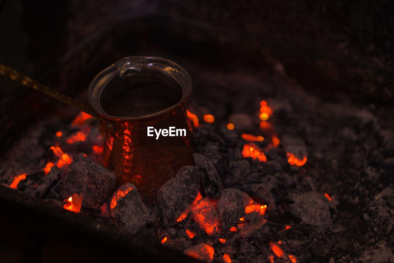 Antique copper sauce pan on burning coal