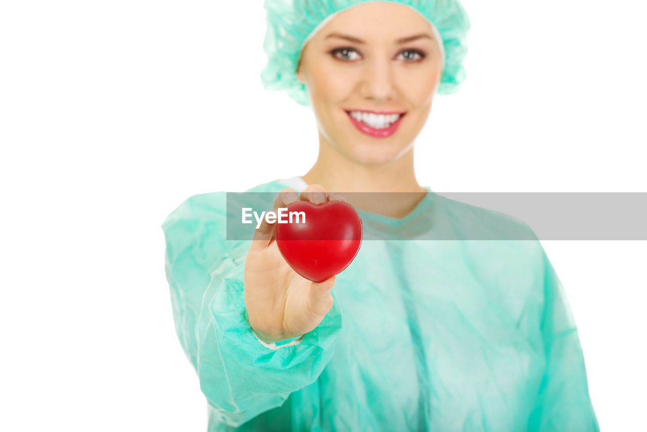 Portrait of female surgeon holding heart shape against white background