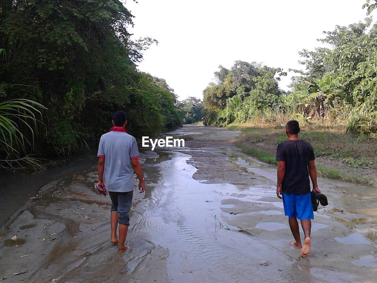 Rear view of men walking on wet landscape against sky