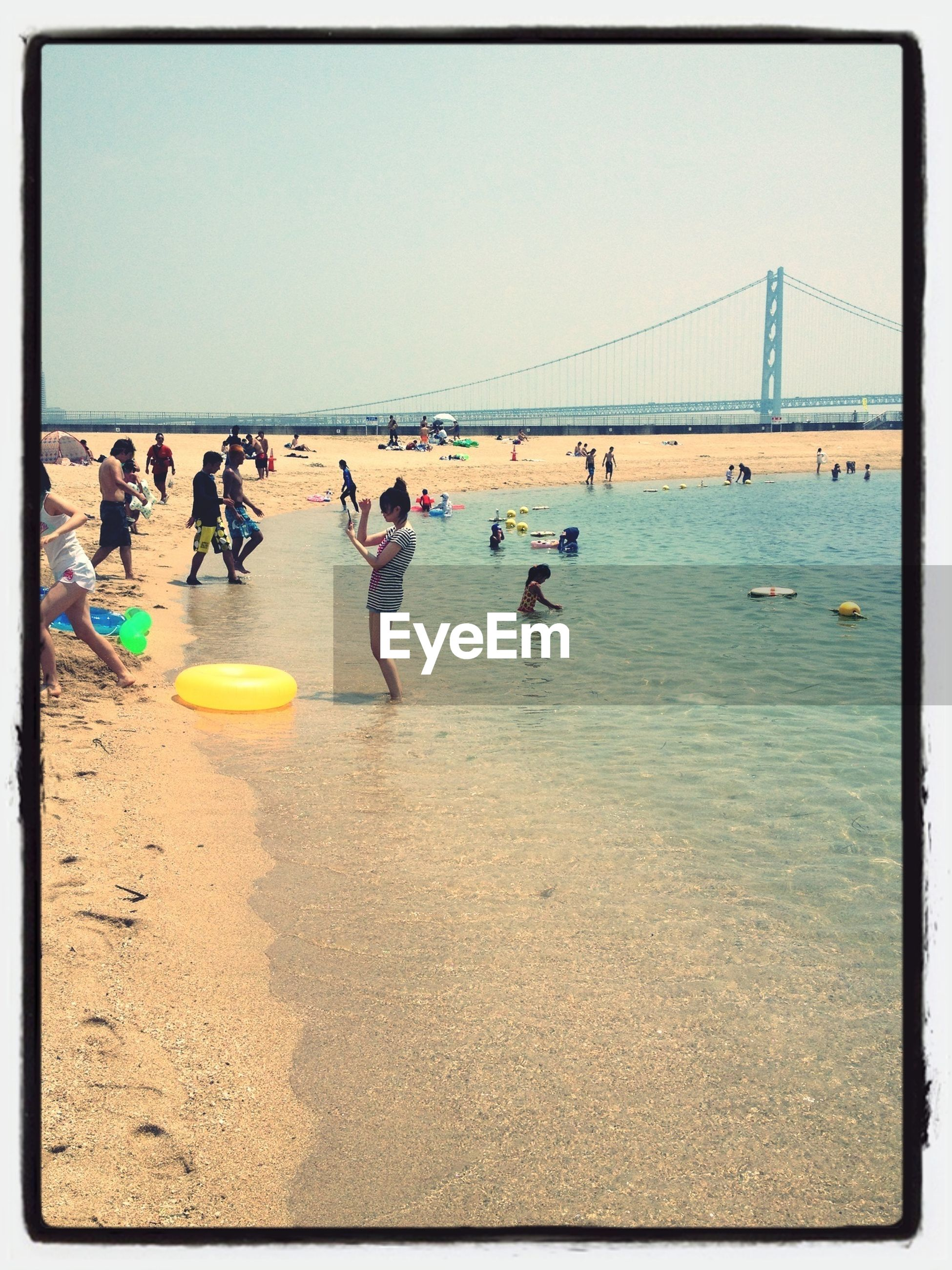 transfer print, sea, water, large group of people, auto post production filter, beach, clear sky, leisure activity, lifestyles, transportation, men, shore, mixed age range, enjoyment, vacations, horizon over water, sand, person, day